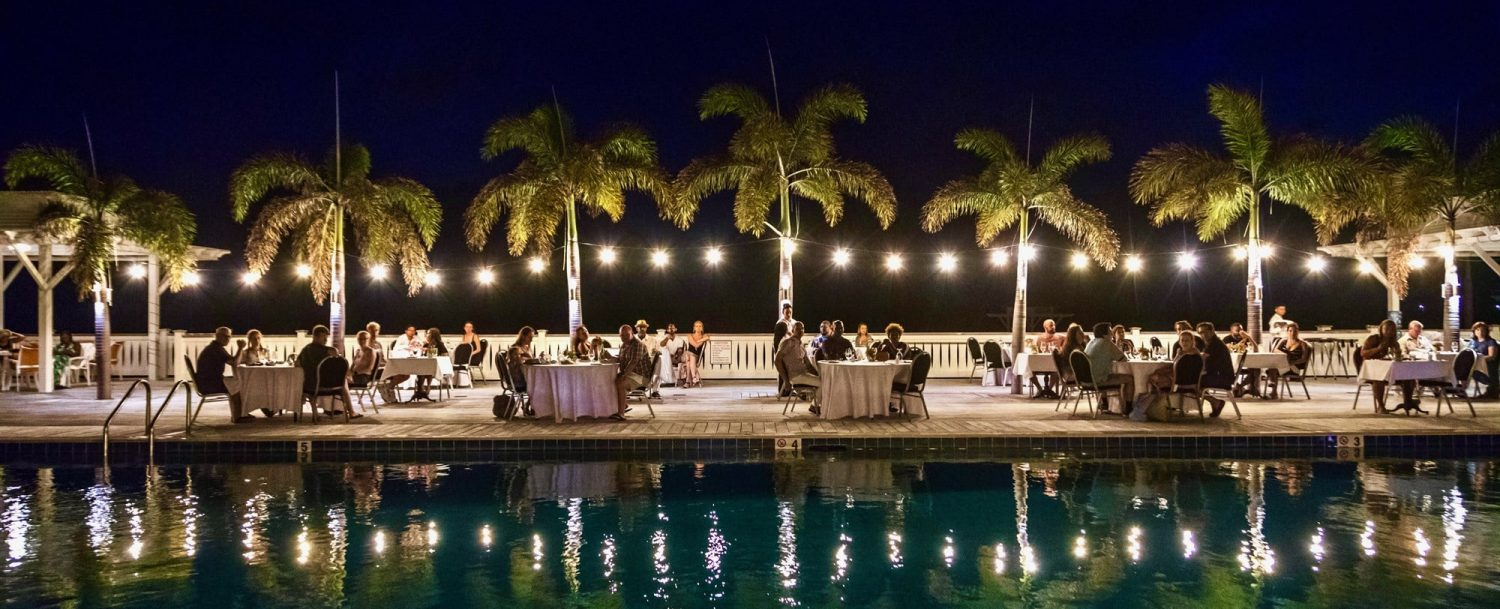 Outside dining by pool at night
