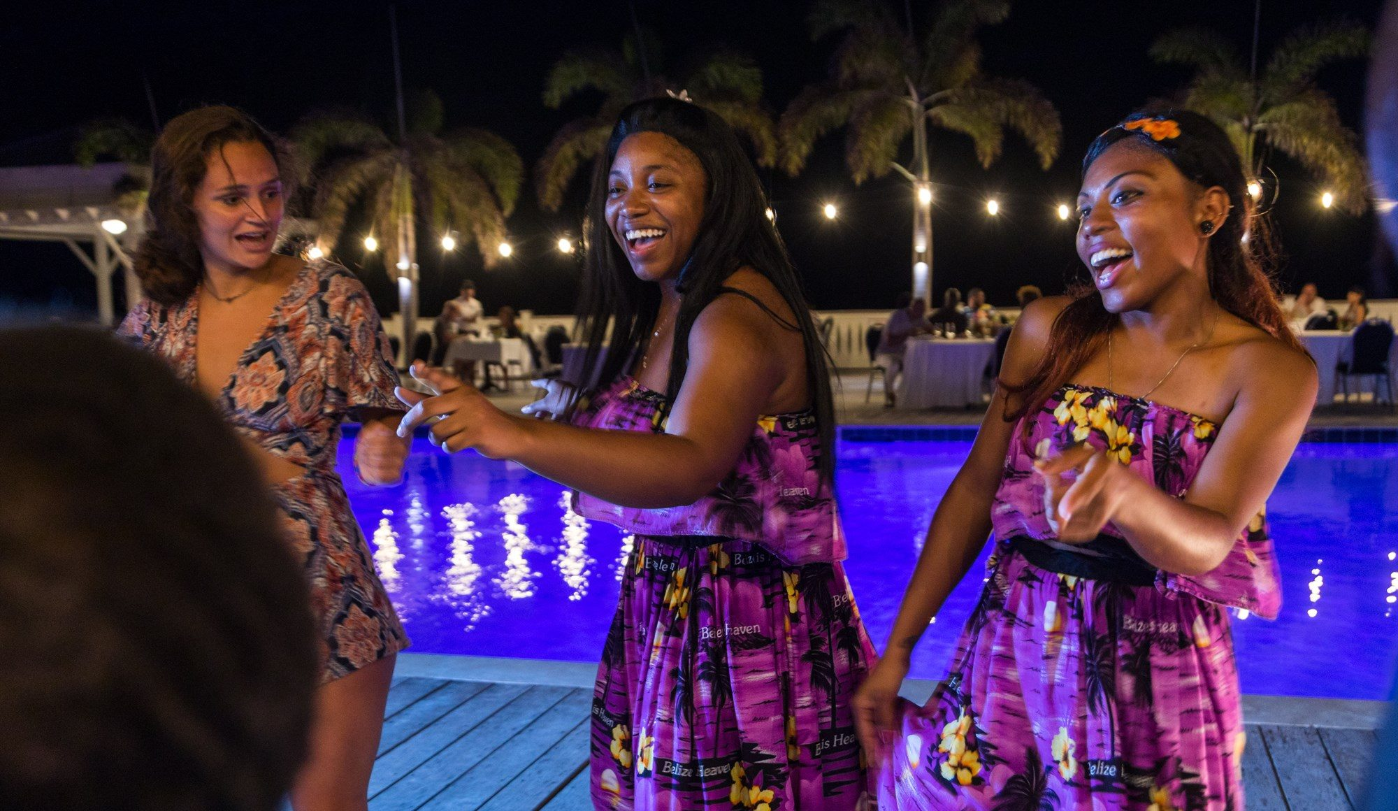 Women dancing at night by the pool