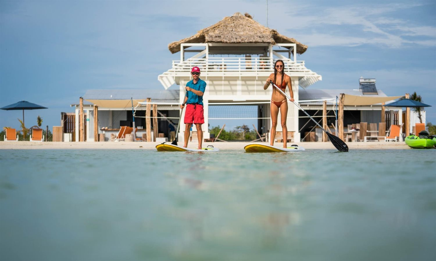 Couple paddleboarding at beach club